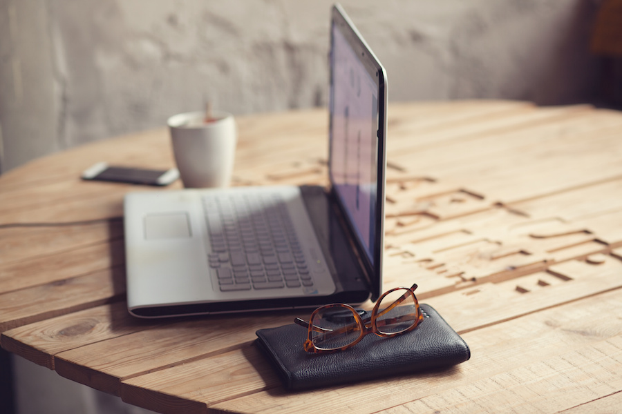 Wooden table with laptop, glasses, wallet and cup of coffee